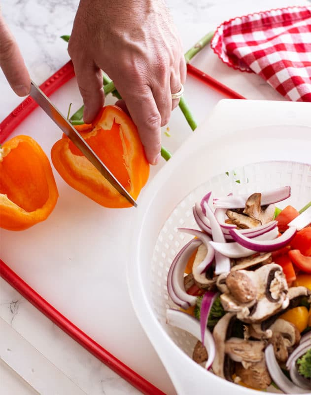 Slicing an orange pepper on a cutting board, colander of fresh chopped vegetables on white marble table.