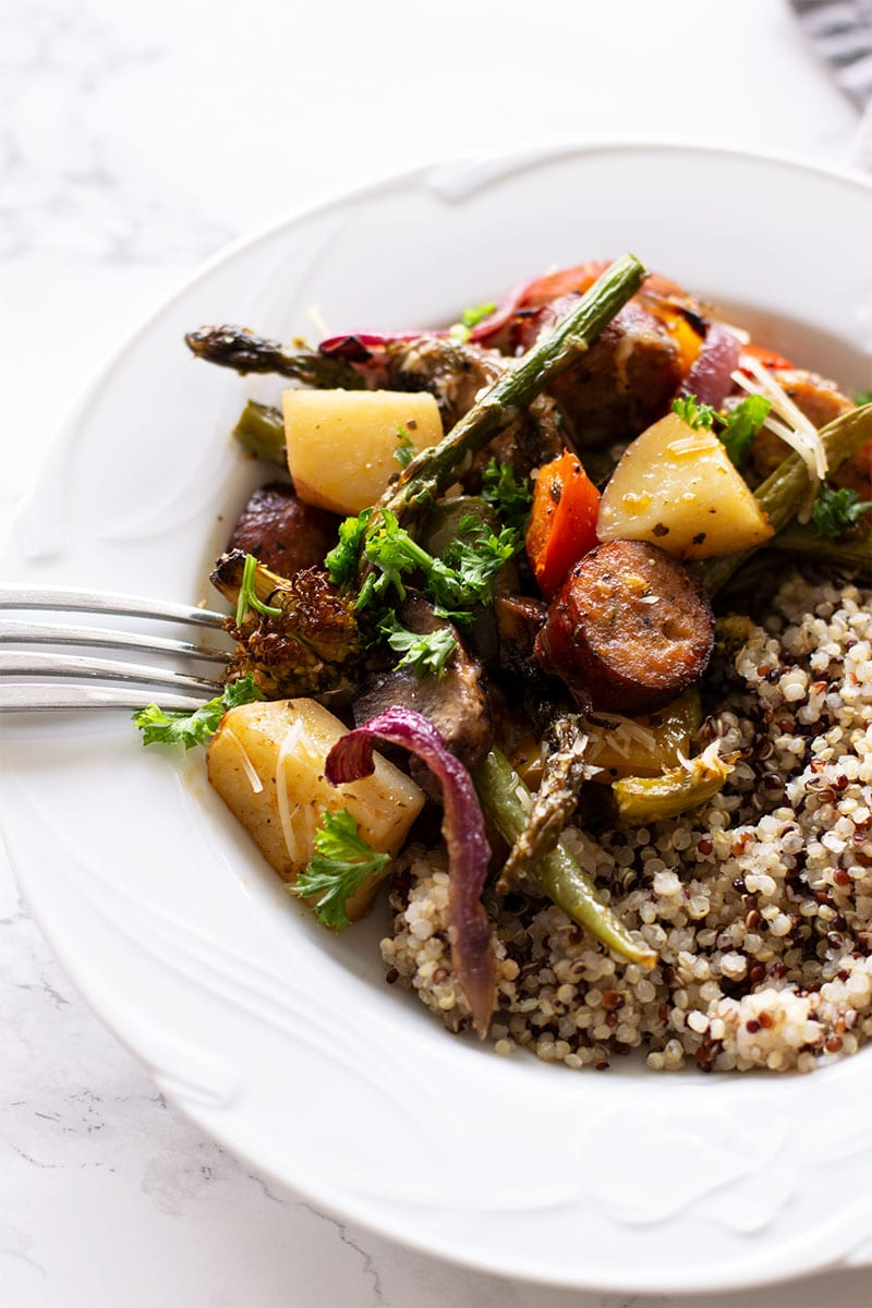 White bowl containing One Pan Smoked Sausage and Vegetables served with quinoa.