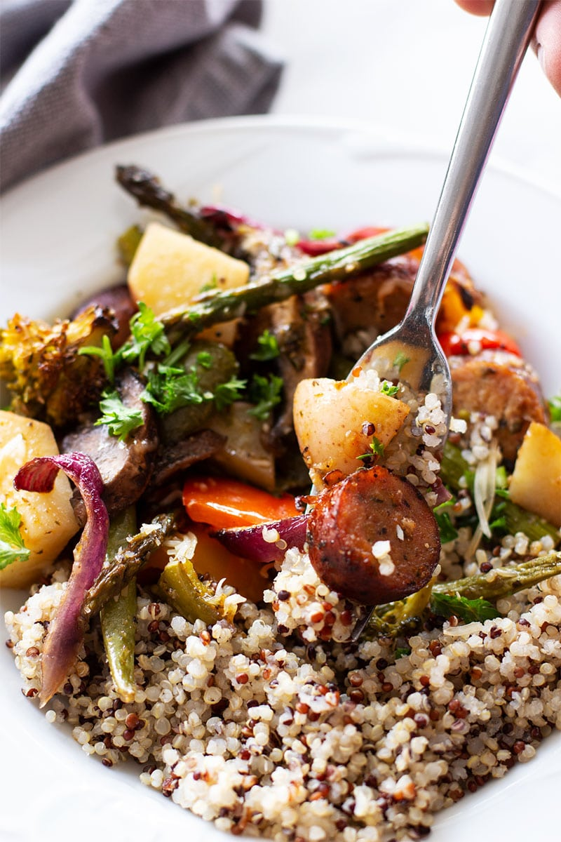 Fork containing smoked sausage with fresh baked potatoes, asparagus, and broccoli, served with cooked quinoa.