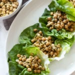 White dish containing 4 Pesto Chickpea Lettuce Wraps sitting on a white marble table.