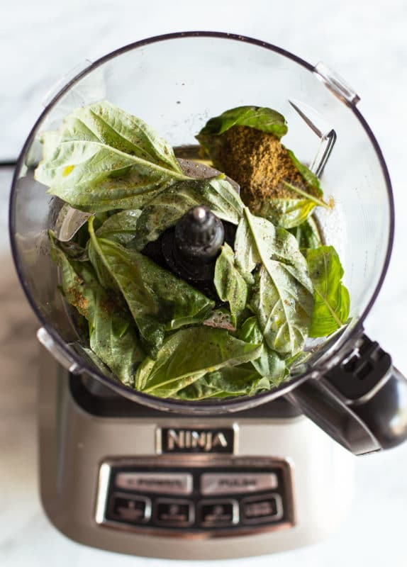 Food Processor containing bay leaves, cumin and other ingredients to make a pesto sauce.