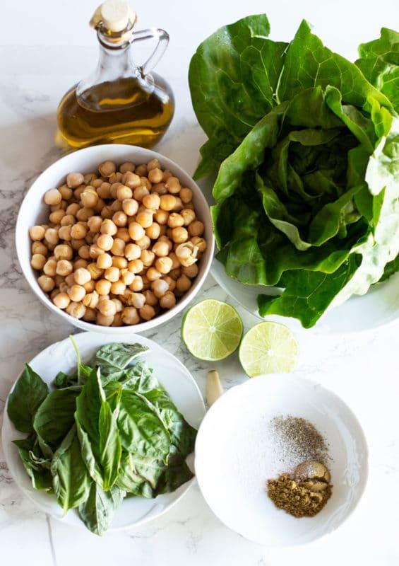 Ingredients for Pesto Chickpea Lettuce Wraps, Bibb lettuce, olive oil, chickpeas, basil leaves, garlic, lime, cumin, salt and pepper.