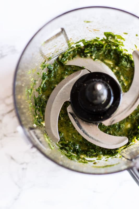 Food Processor containing freshly blended pesto sauce.