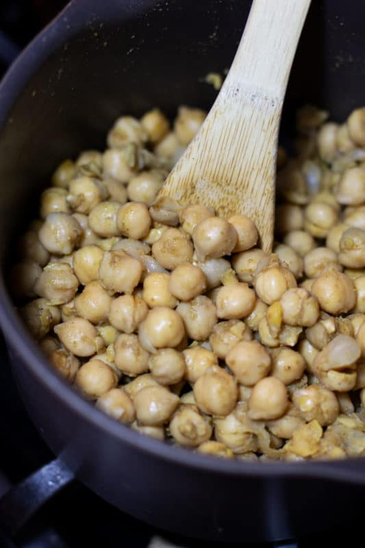 Saucepan containing cooked chickpeas, wooden spoon in pan.