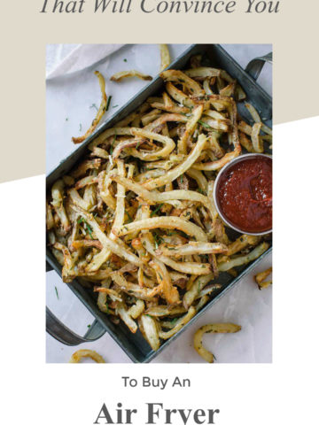 Metal pan containing air fryer french fries topped with parsley and Parmesan cheese, ketchup on table.