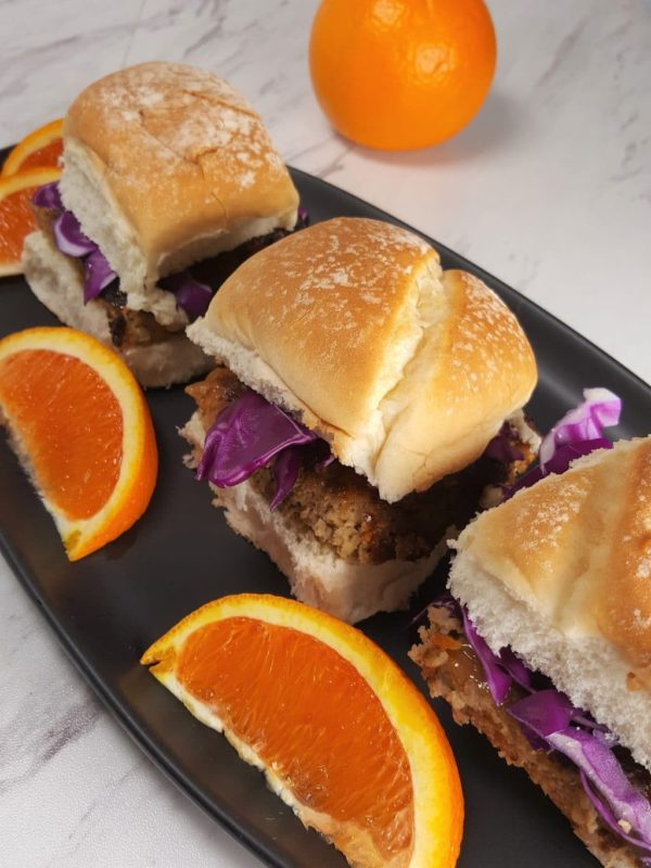 Black plate containing 3 Air Fryer Orange Turkey Burgers With Orange Aioli with purple cabbage and orange slices.