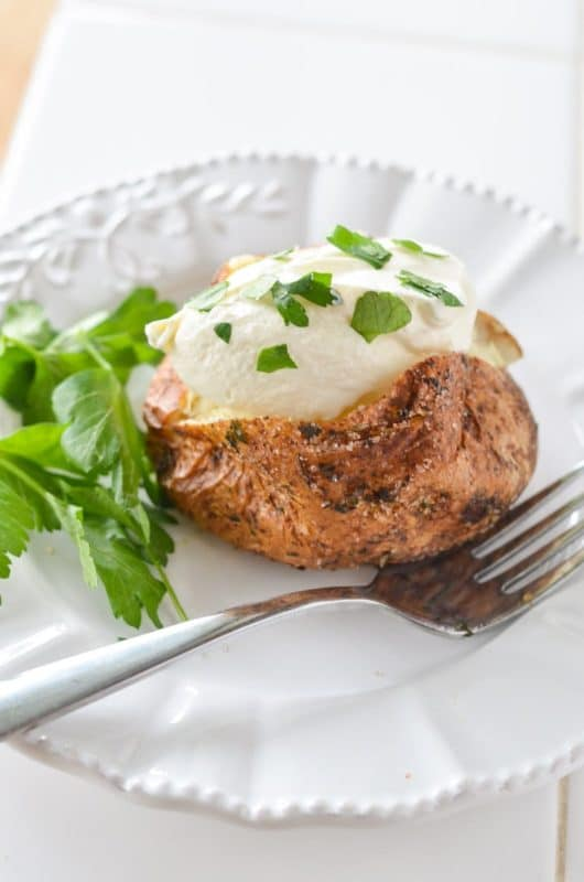 White plate containing an Air Fryer Baked Potato topped with sour cream and chives, fork on side.