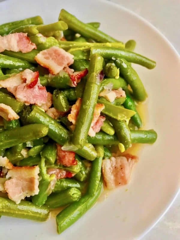 Cooked Green beans with bacon in a white plate cooked in an Instant Pot.