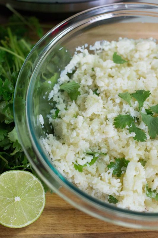 Glass bowl containing cauliflower cilantro rice topped with cilantro, lime on wooden table.