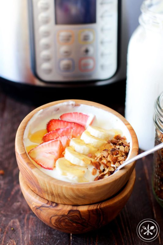 Brown bowl containing homemade Greek Yogurt made in an Instant Pot topped with strawberries, bananas and granola.