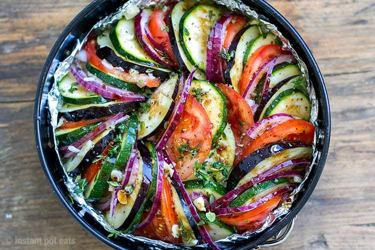 Black Instant Pot Pan containing Ratatouille with tomatoes, zucchini, eggplant, bell peppers, onion, garlic, thyme, basil and marjoram.