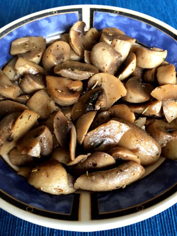 Blue bowl containing sauteed mushrooms cooked in an Instant Pot topped with fresh ground pepper.
