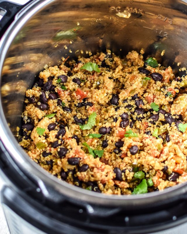 Instant Pot containing Mexican quinoa, black beans and fresh cilantro leaves.