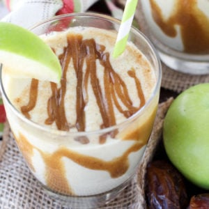 A close up of a glass cup filled with a protein shake, topped with Apple and Caramel.