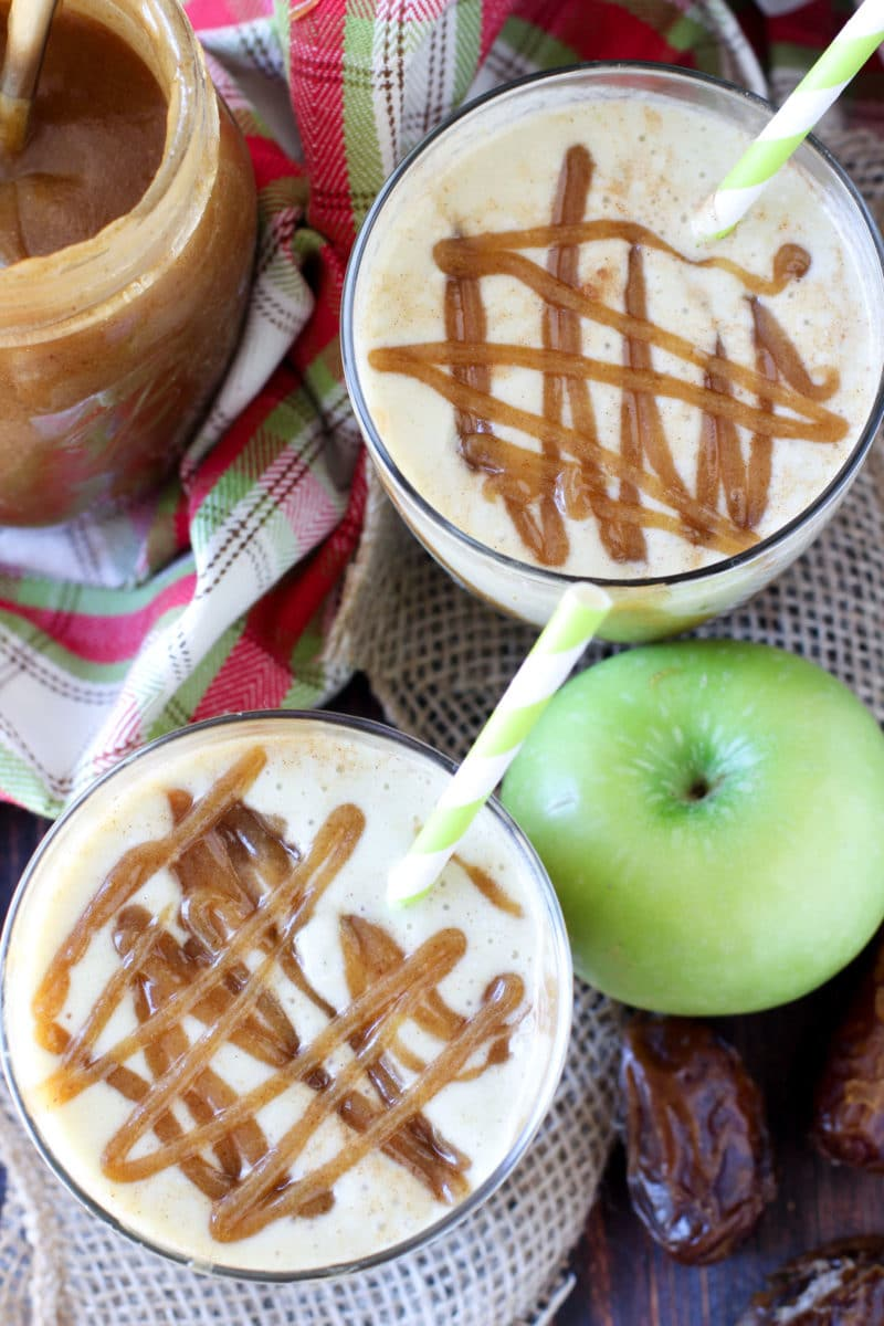 2 Caramel Apple Protein Smoothie in glasses on a table topped with caramel date sauce, green apples and dates on table.