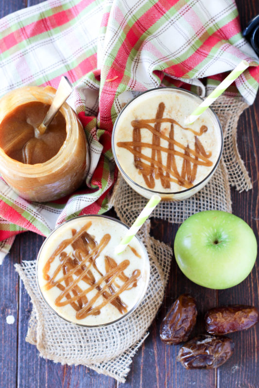2 classes of Caramel Apple Protein Smoothie on a wooden table, caramel sauce, dates and green apples on table.