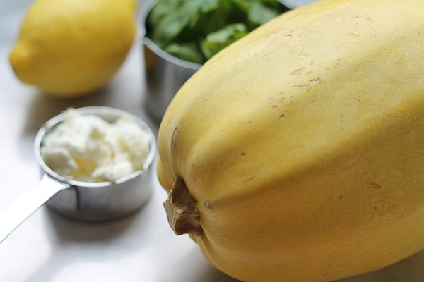 A whole spaghetti squash with a cup of goat cheese, fresh lemon and arugula in the background.