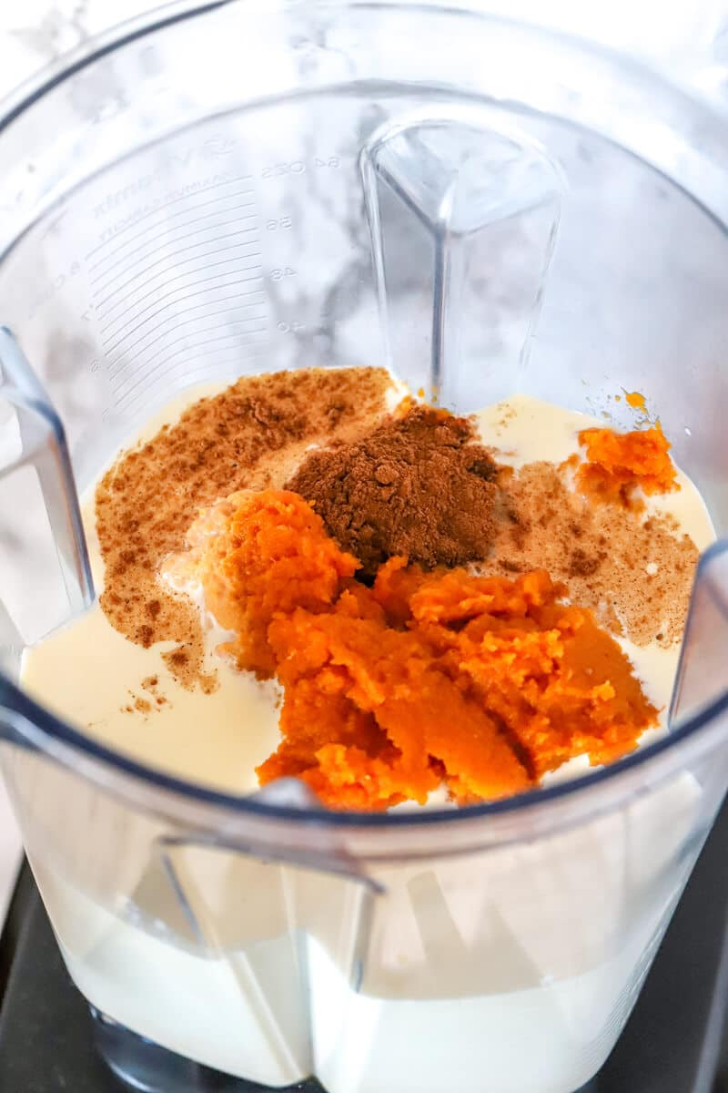 Blender containing ingredients to make pumpkin gelato: pumpkin puree, whole milk, heavy cream, pumpkin pie spice and maple syrup.
