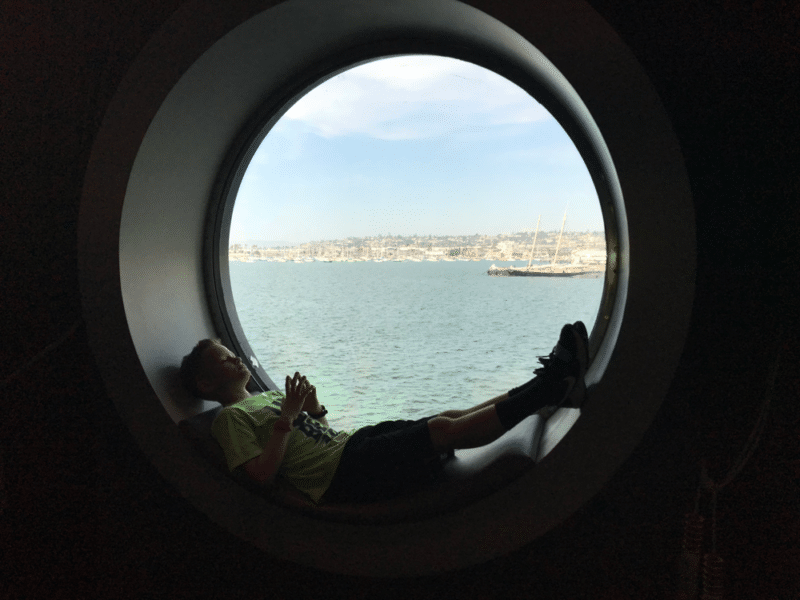 Relaxing in a circular window frame on The Disney Wonder Cruise Ship.