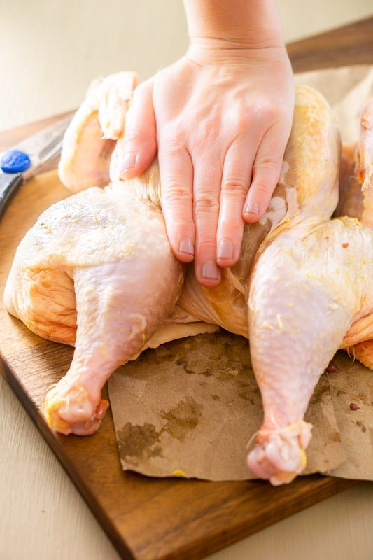 A person breaking the backbone of a raw chicken.