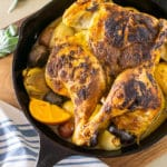 Cast iron skillet containing a roasted apple cider spatchcock chicken with orange and potatoes.