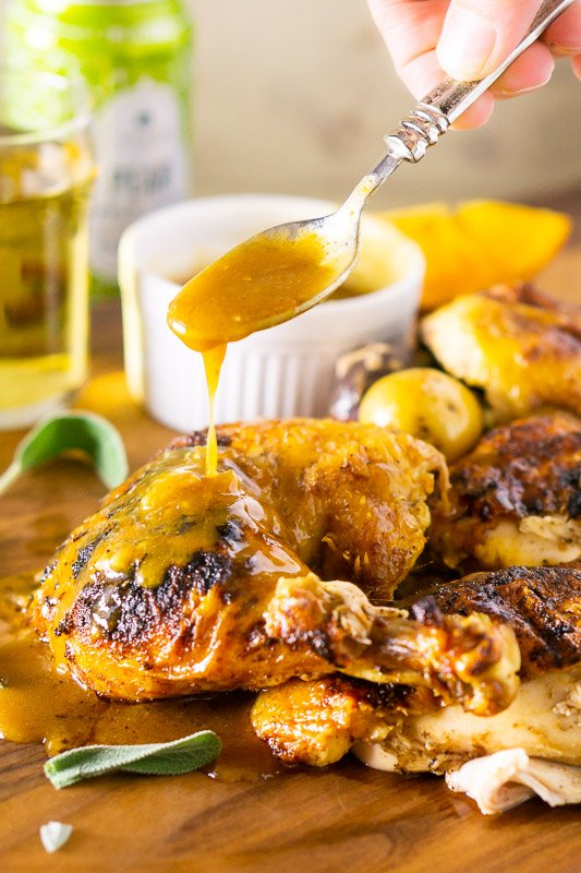 Roasted apple cider spatchcock chicken on a brown table, spoonful of savory sauce dripping onto chicken.