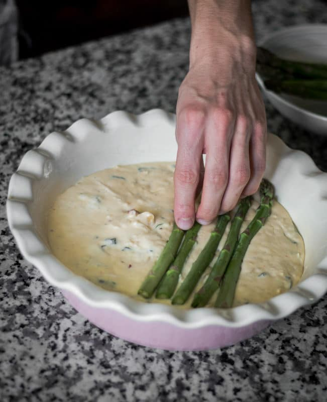 A hand placing asparagus spears neatly on top of a raw quiche mixture.