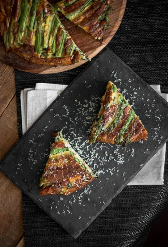 2 slices of an asparagus and tomato filled crustless quiche on a black slate plate topped with Parmesan cheese, quiche on table.