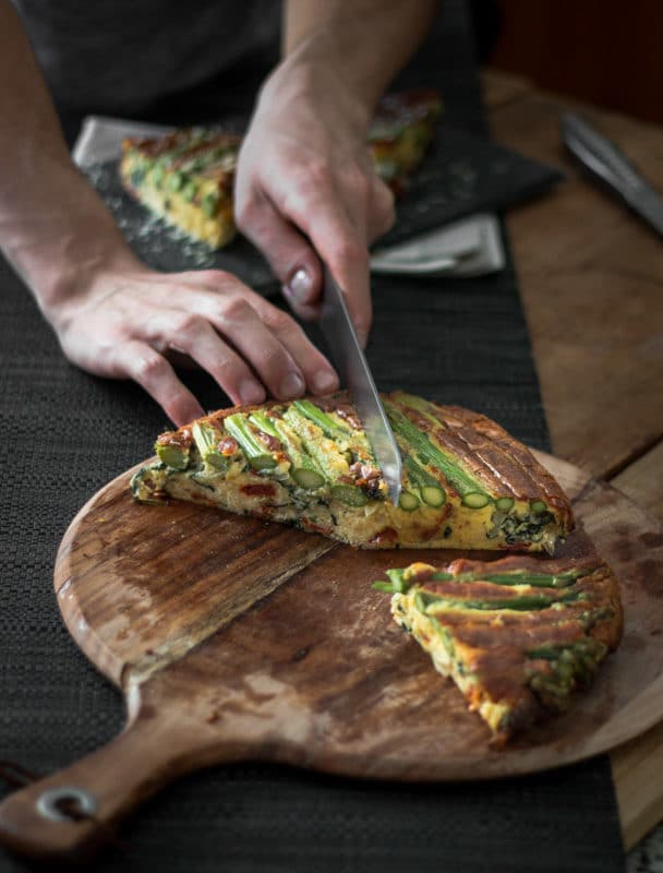 A photo of someone slicing portions out of an asparagus and tomato filled crustless quiche.