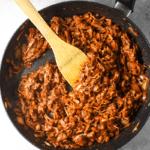 Pan containing jackfruit, salt, smoked paprika, cumin, chili powder, onion powder, cane sugar, chipotle peppers, adobo sauce, soy sauce, water, and lime juice to make jackfruit tacos.