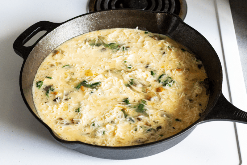 uncooked veggies and egg mixture in a cast iron skillet for Hearty Spinach Frittata