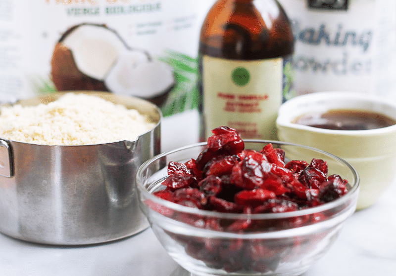Ingredients to make Cranberry Cookies including almond flour, dried cranberries, coconut oil and maple syrup.