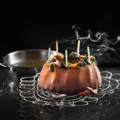 A photo of a bundt cake with blown out candles on them.