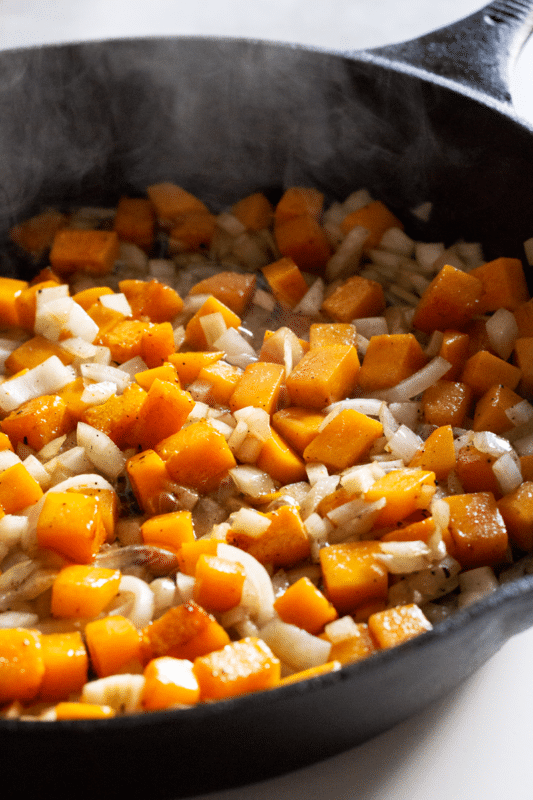 Diced butternut squash and onions cooking in a cast iron pan.