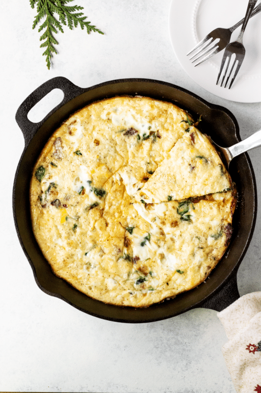a slice of Hearty Spinach Frittata being lifted out of a cast iron skillet. A white plate with two silver forks and a sprig of evergreen are at the top of the image.