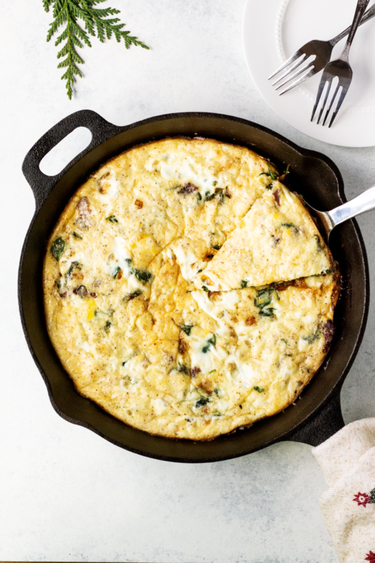 Overhead shot of Hearty Spinach Frittata in a cast iron skillet with a slice being lifted out and a white plate and two forks in the upper right.