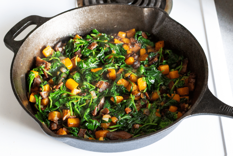 veggies and bacon in a single layer in a cast iron skillet for Hearty Spinach Frittata