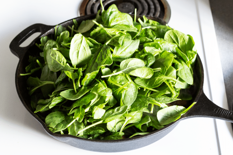 Spinach in a cast iron skillet before wilting.