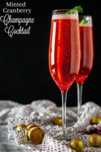 2 Champagne Flutes filled with a minted cranberry champagne cocktail topped with a sprig of mint.