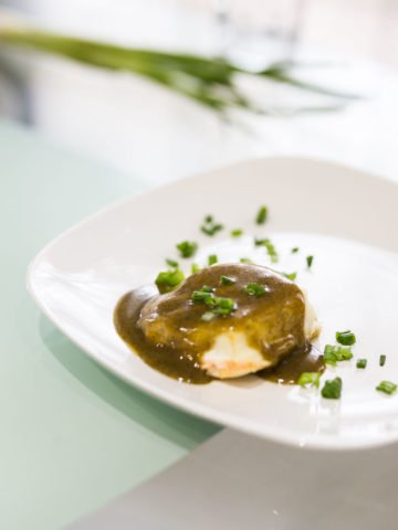 White plate containing cod fish topped with pesto and scallions.