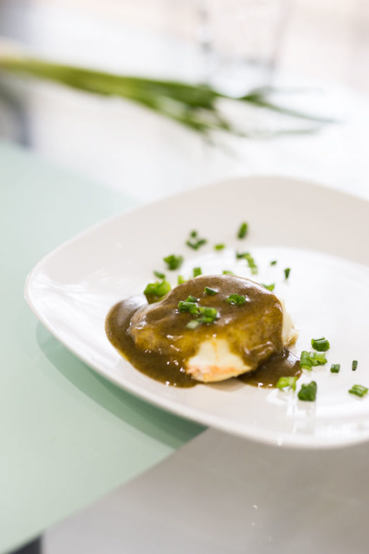 While plate containing cooked cod filet drizzled with pesto sauce topped with fresh scallions.