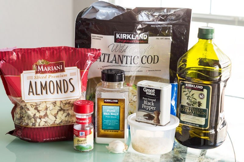 Ingredients for making pesto cod fish, almonds, basil, cod, salt, black pepper, Garlic, olive oil and Parmesan cheese.
