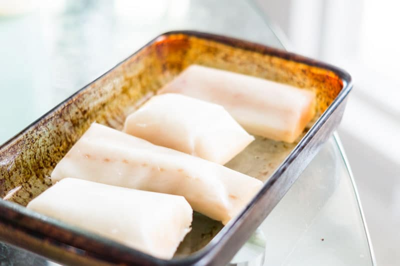 Pyrex dish containing 4 frozen cod fish filets.