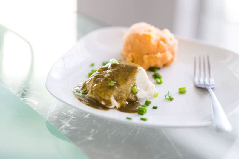 While plate containing cooked cod filet drizzled with pesto sauce, fork on plate.