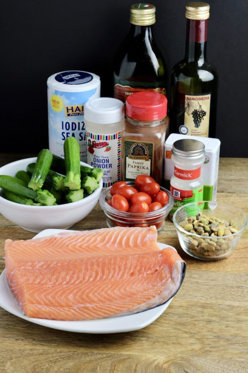 One pan pistachio salmon ingredients including salmon, zucchini, tomatoes, pistachios, salt, onion powder, paprika, garlic powder, olive oil and balsamic vinegar.