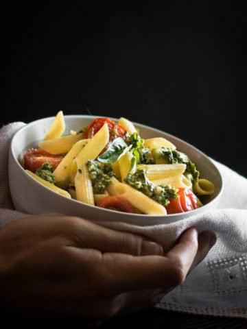 A white bowl filled with guten free pasta, pesto and cherry tomatoes.