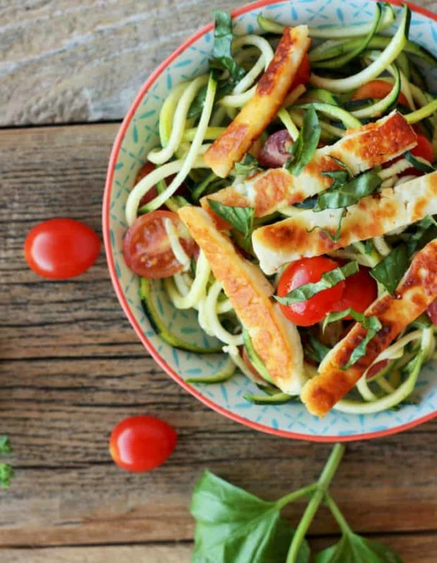 Bowl containing Fried Halloumi with Bruschetta Zoodles sitting on a brown table topped with basil and tomato.