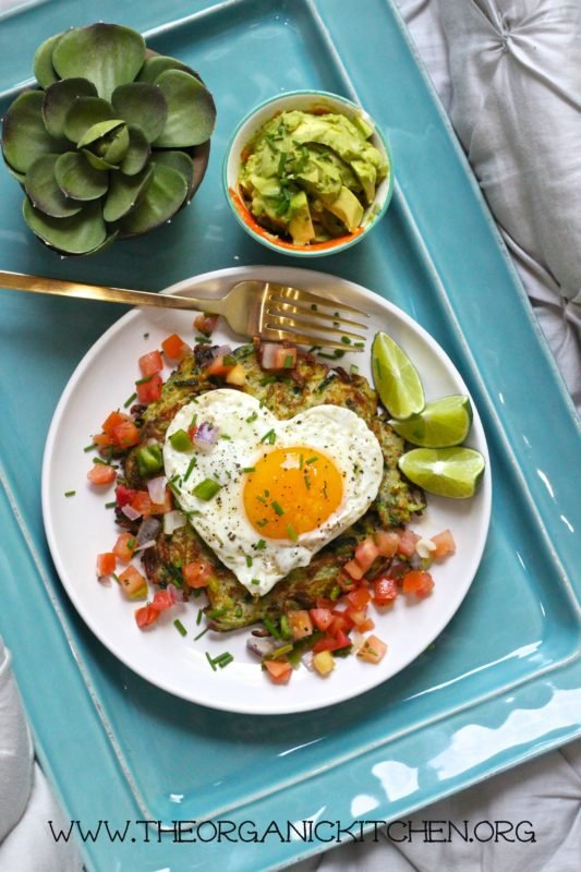 White plate sitting on a blue tray containing Paleo-Whole 30-Keto Huevos Rancheros, fork and avocado on tray.
