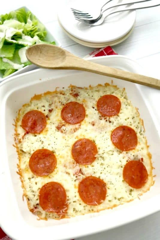 White pyrex dish containing pizza casserole made with cauliflower and topped with pepperoni.