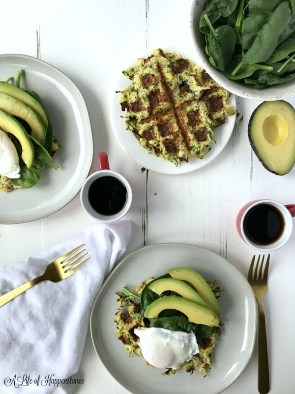 White plate containing Zucchini Squash Waffles topped with avocado.